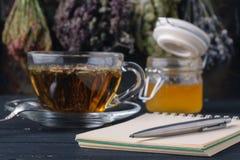 Recipe of healing herbal tea with open notebook Stock Photos