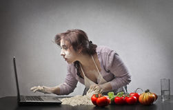 Recipe on Internet. A woman, while is cooking, searching a recipe on a laptop computer Royalty Free Stock Photos