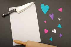 Recipe for love. A knife and a rolling pin framing an empty piece of paper next to some colorful heart cutouts - for your favorite recipe or recipes for love Stock Photo