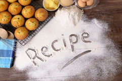 Cake baking ingredients, recipe word written in white flour. The word Recipe written in flour on a dark wood table with freshly baked muffins and ingredients Royalty Free Stock Photos