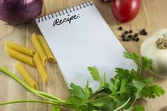 Recipe note card. Blank note card for recipe on wood table with tomato, onion, garlic, pepper, pasta and parsley Stock Image