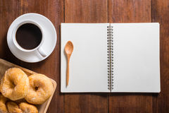 Recipe notebook, donuts, Coffee cup on wooden background, top vi. Recipe notebook, donuts, Coffee cup top view on wooden table Royalty Free Stock Photo