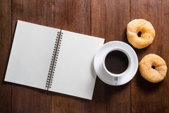Recipe notebook, donuts, Coffee cup on wooden background, top vi Stock Images