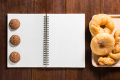Recipe notebook, donuts, cookie on wooden background Stock Image