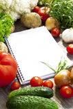 Recipe notebook and fresh vegetables Stock Images