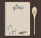 Recipe notebook graph with hand drawn text, oilcan and mortar. Olive leaves. Spoon fork. Wooden background Royalty Free Stock Image
