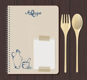 Recipe notebook graph with hand drawn text, oilcan and mortar. Wooden fork and spoon. White notebook sheet and adhesive tape. Wooden background Royalty Free Stock Image