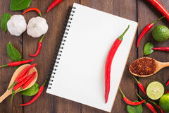 Recipe notebook,  Red chilli, garlic and lemon on wooden backgro Royalty Free Stock Image