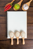Recipe notebook, rice, Red chilli, garlic and lemon on wooden ba Stock Images