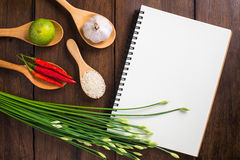 Recipe notebook, rice, Red chilli, garlic and lemon on wooden ba Stock Photos
