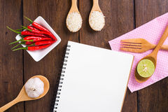 Recipe notebook, rice, Red chilli, garlic and lemon on wooden ba Stock Image