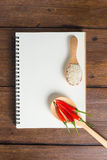 Recipe notebook, rice, Red chilli on wooden background Royalty Free Stock Photo