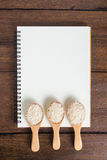 Recipe notebook, rice in wooden spoon on wooden background Stock Photos