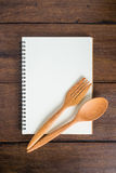 Recipe notebook, spoon, fork on wooden background Stock Image