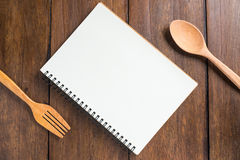 Recipe notebook, spoon, fork on wooden background Stock Photography