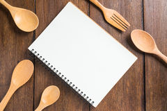 Recipe notebook, spoon, fork on wooden background Royalty Free Stock Photography