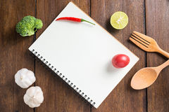 Recipe notebook, tomatoes, Red chilli, garlic and lemon on woode Stock Image