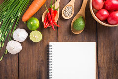 Recipe notebook, tomatoes, Red chilli, garlic and lemon on woode Stock Images