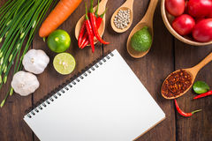 Recipe notebook, tomatoes, Red chilli, garlic and lemon on woode Royalty Free Stock Photos