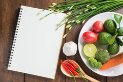 Recipe notebook, tomatoes, Red chilli, garlic and lemon on woode Stock Photography