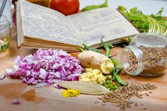 Notes with recipes surrounded by spices and vegetables on a wooden table in the kitchen royalty free stock photography