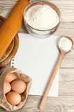 Recipe paper and baking cake ingredients. On a wooden table Royalty Free Stock Photos