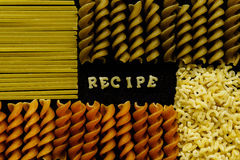 Recipe sign arranged by pasta, close up on black Royalty Free Stock Photo