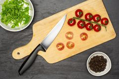 Recipe step by step farfalle with arugula leaves on grey stone. Slicing cherry tomatoes step. recipe step by step farfalle with arugula leaves on chopping board stock photos