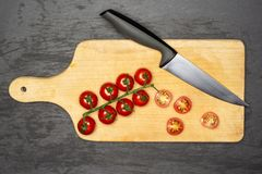 Recipe step by step farfalle with arugula leaves on grey stone. Slicing cherry tomatoes. recipe step by step farfalle with arugula leaves on chopping board stock images