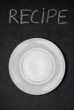 Recipe title written white chalk and empty plate on a blackboard Royalty Free Stock Image