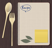 Recipes Notebook. With wood spoon and fork over wooden table Stock Images
