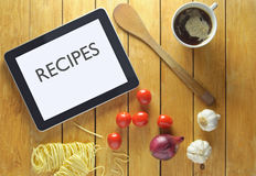 Recipes on a tablet. Tablet with recipes heading on a table surrounded by fresh food ingredients Royalty Free Stock Photo