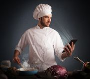 Recipes on the tablet. Man chef cooking while reading on tablet Royalty Free Stock Images