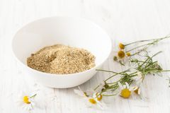 Dry chamomile flowers in a bowl on a white table Royalty Free Stock Photo