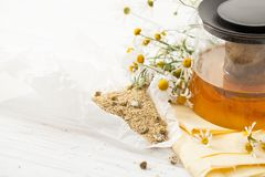 Dry chamomile flowers with a broth on a white table Royalty Free Stock Photography