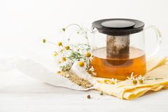 The broth in the kettle with the Daisy flowers on a white table Stock Photo