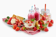 Recipes using fresh ripe strawberries over white. With a waffle and cream, muesli topped with yogurt and berries, smoothies, infused water and whole fruit stock photography