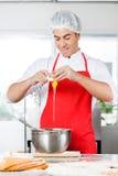 Recipiente de Breaking Egg In do cozinheiro chefe ao preparar-se Fotografia de Stock