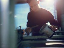 Recipiente de derramamento do homem com cor de prata na oficina imagens de stock