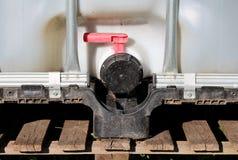 Recipiente de maioria intermediário ou de água plástico de IBC tanque com a gaiola do metal e a grande válvula postas sobre a pál fotografia de stock royalty free