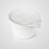 Recipiente di plastica bianco con il coperchio della stagnola su gray Immagine Stock