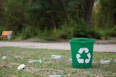 Recipiente di riciclaggio luminoso accanto alle bottiglie di plastica su uno sfondo naturale Contenitori per il riciclaggio dei r Fotografia Stock