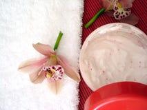 Recipiente do creme hidratando do cosmético com orquídeas cor-de-rosa e t imagem de stock