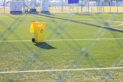Recipiente giallo su erba artificiale in stadio di calcio Fotografia Stock Libera da Diritti