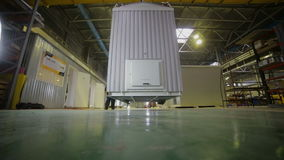 Recipiente movente do trabalhador masculino em um armazém enorme usando o guindaste industrial filme