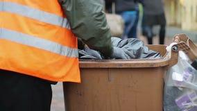 Recipiente para residuos de limpieza del barrendero de calle en el cuadrado de ciudad, trabajando difícilmente en el salario bajo metrajes