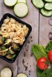 Recipiente plástico com as asas de galinha e os vegetais crus grelhados no fundo rústico, salada dos vegetais imagem de stock royalty free