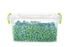 Recipiente plástico com ervilhas congeladas foto de stock