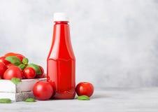 Recipiente plástico com molho da ketchup de tomate com os tomates crus no fundo da pedra da cozinha imagem de stock royalty free