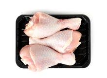 Recipiente plástico com os pilões de galinha crus no fundo branco, vista superior fotografia de stock